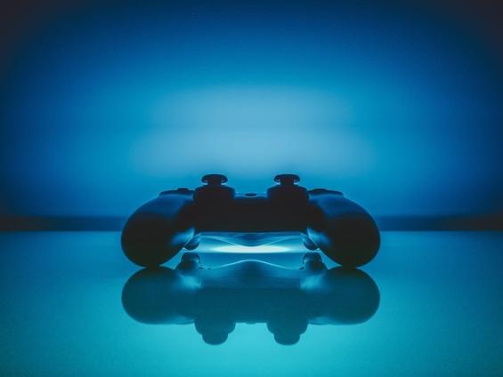 暗い室内で光るPS4のコントローラーの